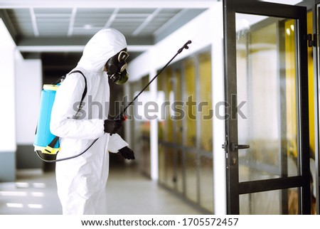 Disinfecting of office to prevent COVID-19, Man in protective hazmat suit with  with spray chemicals to preventing the spread of coronavirus, pandemic in quarantine city. Cleaning concept. #1705572457