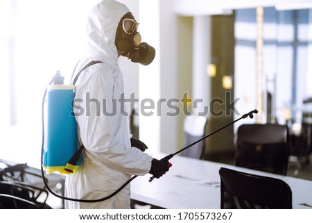 Disinfecting of office to prevent COVID-19, Man in protective hazmat suit with  with spray chemicals to preventing the spread of coronavirus, pandemic in quarantine city. Cleaning concept. #1705573267