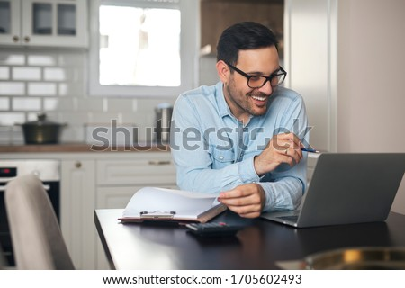 Young man working from home doing paperwork while using laptop and holding pen in his hand. #1705602493