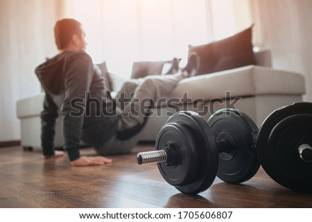 Young ordinary man go in for sport at home. Hardworking beginner sit on floor and hold legs on sofa. Freshmen trying to do abs exercising. Home alone doing workout. Dumbbells on floor. #1705606807