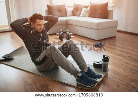 Young ordinary man go in for sport at home. Hardworking freshman sit on mat and do abs excercise. Not easy to start workout alone in apatment. Beginner in action. Sport equipment on floor. #1705606813