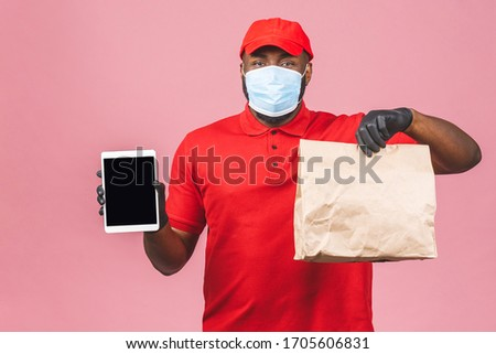 Delivery man employee in red cap blank tshirt uniform face mask glove hold empty cardboard box isolated on pink background. Service quarantine pandemic coronavirus flu virus 2019-ncov.  #1705606831