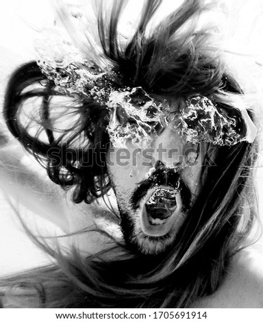 Artistic pic out of focus underwater with long hair man swimming with bubble in water, dark underwater atmosphere with nightmare human abyssal creature like mermaid with beard