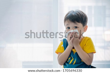 Little boy blowing nose into tissue paper and wearing surgical face mask. Copy space. #1705696330