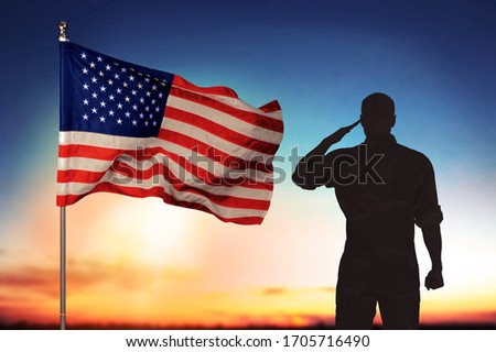 Young military soldier man silhouette on sunset background with USA flag
