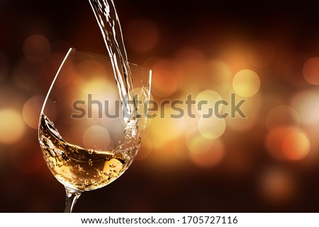 White wine being poured in the wineglass
