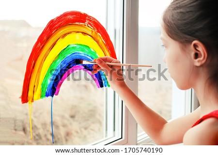 Schoolgirl draws rainbow sign of hope on window. #1705740190