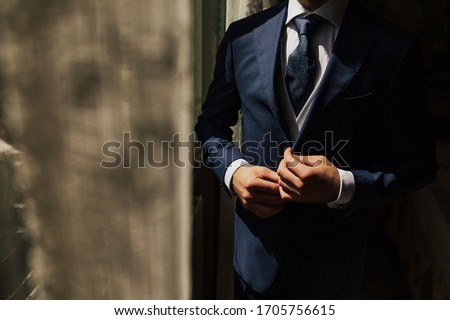 Grooms morning preparation. Cropped photo of elegant young fashion man dressing up for wedding celebration. Groom dressed in modern blue formal suit, white shirt getting ready for event. Sunny morning #1705756615