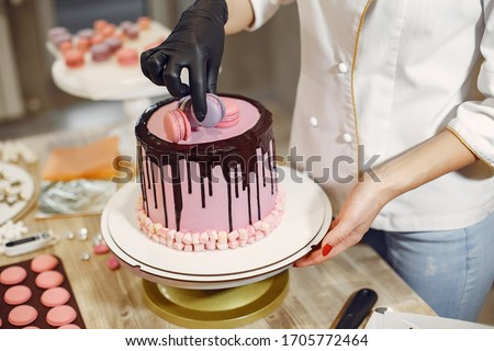 Confectioner in a kitchen. Woman in a uniform. Professional decorates the cake. Royalty-Free Stock Photo #1705772464