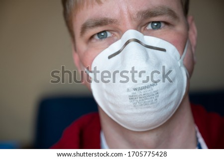 front view of middle aged white Caucasian male with blonde hair wearing a N95 protective mask #1705775428