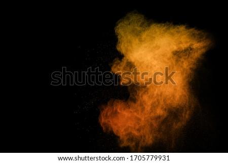 Orange powder explosion on black background. Colored cloud. Colorful dust explode. Paint Holi. #1705779931