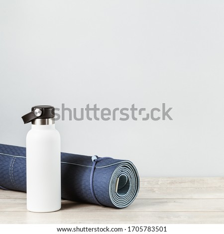 Rolled blue yoga mat and white metal water bottle flask on grey wooden surface. Gender neutral fitness and exercise concept and hydration with copy space #1705783501