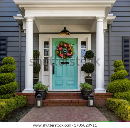 Beautifully decorated front door of traditional home. Brick path and trimmed hedges. Royalty-Free Stock Photo #1705820911