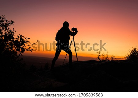 Awesome Sunset Background taken on top of a Mountain (Feldberg) - Silhouette of a Young Woman taking a Picture of the beautiful orange purpleish Colourfull Sunset with a Camera standing on a Tripod.
