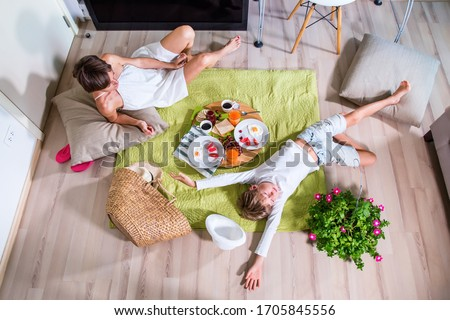 Happy mom and boy imitating summer picnic time on green grass blanket near TV screen. Travelling with family. Coronavirus situation in tourism industry. Quarantine. Stay at home. Isolation. Top view #1705845556