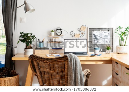Place for work at home with wooden office desk  and laptop with empty screen with mock up. Home office while coronavirus. Cozy interior in scandinavian style with white wall with copy space.