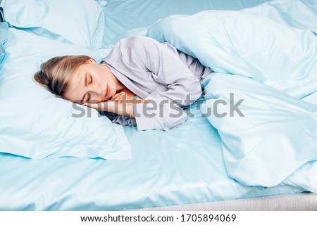 Beautiful girl alone sleeps in bed. A young woman lies on blue silk bedding on a hotel bed. Blue bedding made of natural silk. #1705894069