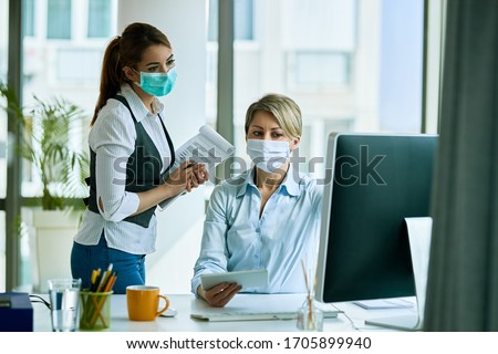 Female business colleagues with face masks working in the office and reading an e-mail on a computer.  #1705899940