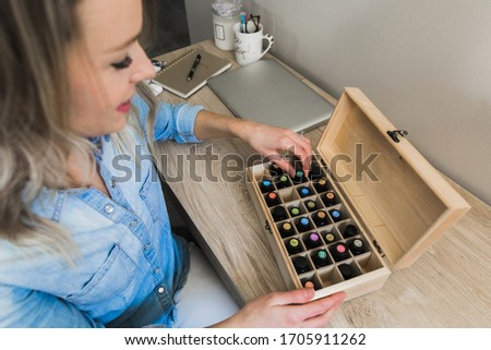Young woman choosing an essential oil from her essential oil storage box #1705911262