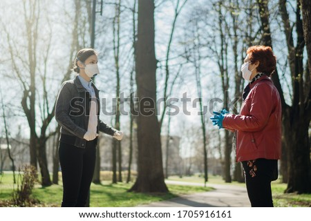Elderly woman with protective face mask/gloves talking with a friend.Coronavirus COVID-19 disease protection.Conversation from a safe distance.Socialization restriction.Social distancing practice #1705916161