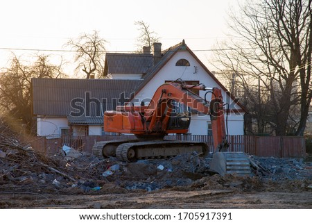 Excavator demolishes an old wooden house in the village for new construction project. Tearing Down a Houses. Building removal made of bricks. Hard equipment for demolition works Royalty-Free Stock Photo #1705917391