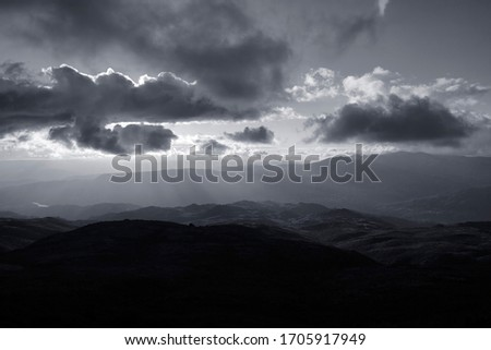 Cloudy mountains at sunset with beautiful light. Converted black and white. Toned blue.