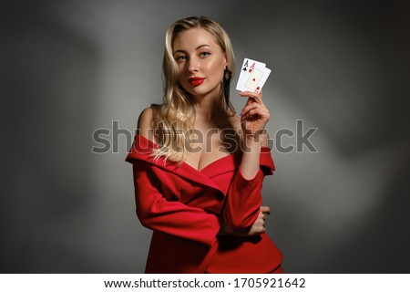 Blonde model in red dress and black earrings. She is showing two aces, posing on gray studio background. Poker, casino. Close-up, copy space Royalty-Free Stock Photo #1705921642
