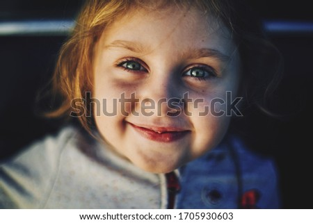 A cheerful portrait of a white-skinned girl with brown hair smiling and looking at the camera. The girl has green eyes and a full smile. Close-up #1705930603