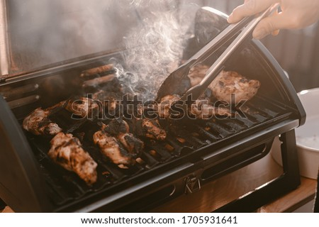 Grill season outdoor in park or balcony. Spring summer grilling. Balcony gas grill. Barbeque fourth of July weekend. Chicken wings on grill. Flame and smoke over grill. BBQ quarantine on balcony. #1705931641