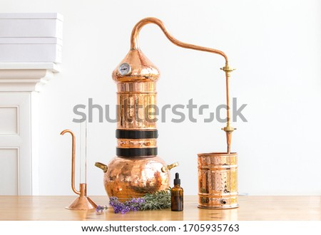 Distilling apparatus alembic with esential oil flowers at the wooden table. Royalty-Free Stock Photo #1705935763