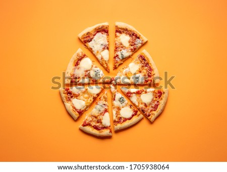 Cheese pizza cut in equal pieces on an orange seamless background. Flat lay of four cheese pizza. Quattro formaggi Italian pizza. #1705938064