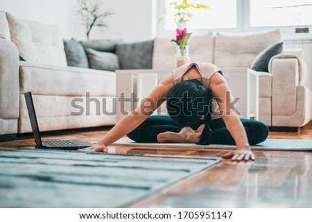 woman meditates and listens to music in front of a laptop #1705951147