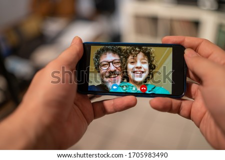Dad and son make a smartphone video call to the relatives while they are in quarantine due to the coronavirus epidemic. People using technology to stay safe and to be near friends and parents. #1705983490