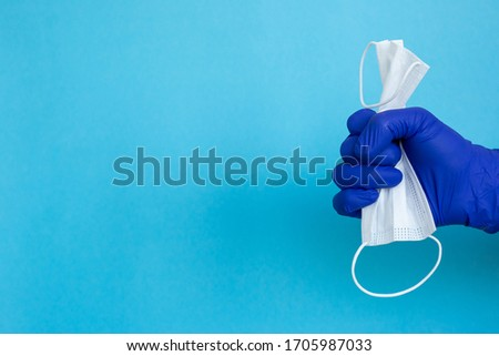 Protective face mask or medical mask in hand protected by blue gloves on blue background. Coronavirus disease. Concept of health and medicine, virus prevention. #1705987033