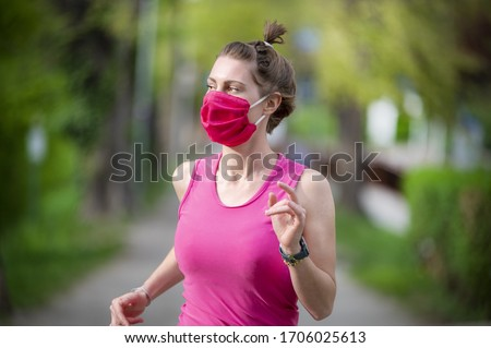 Stay in fit during quarantine. A sportive young woman is jogging outdoor, she have pink protective mask on face. Running  alone on a tree-lined road in the days of the Corona Virus or Covid-19. #1706025613