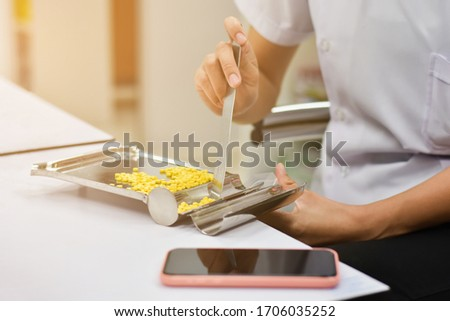 Pharmacist is counting pills on counting drugstore,Pills in pill counting tray,Orange tablets medicine on the drug count tray,Tablets medicine on the drug count tray, #1706035252