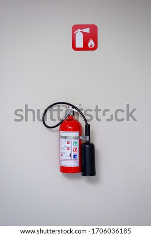 Fire extinguisher and fire department sign on a white wall.