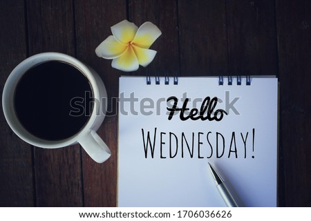 Hello Wednesday. Have a happy, beautiful and productive Wednesday concept. With a cup of morning coffee, text greeting on a notebook, a pen and yellow Bali frangipani flower on desk. Top view. Royalty-Free Stock Photo #1706036626