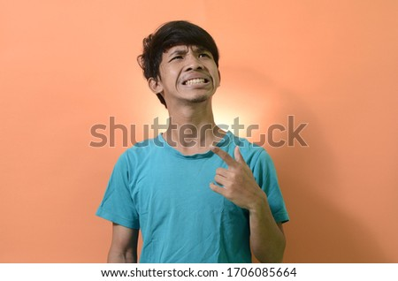 young Asian man wearing a blue shirt with a funny expression on an orange background  #1706085664