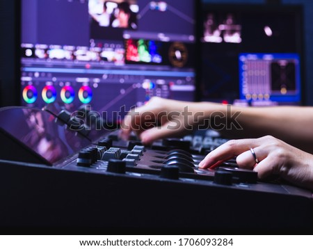 The hand of a person who is operating color grading controller machine in color grading room studio lab for edit video colortone