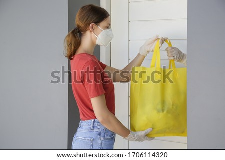 Volunteer women brings a bag with food and another unessesary groceries for persons in need. Delivery to the door. Food delivery services during coronavirus pandemic.	  #1706114320