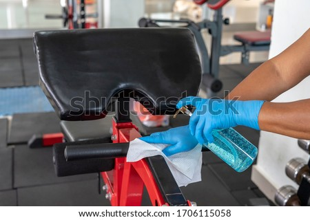 Staff using wet wipe and disinfectant from the bottle spraying sit up bench in gym. Antiseptic,disinfection ,cleanliness and healthcare. Anti bacterial and Corona virus COVID19. #1706115058
