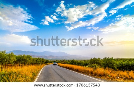 Rural field highway road landscape. Asphalt road on mountain valley. Field asphalt road view. Asphalt road car scene #1706137543