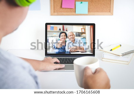 he son talked to his father and mother Asian Elderly Via the video call app on a home notebook computer. Social Distancing concept prevents the spread of the coronavirus. #1706165608