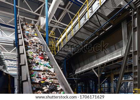 Conveyor belt transports garbage inside drum filter or rotating cylindrical sieve with trommel or sorting pieces of garbage into various sizes fractions at recycling plant #1706171629