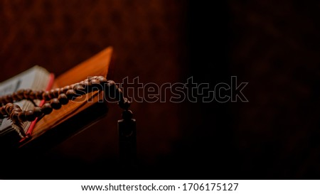 Tasbih or Islamic prayer beads with Quran on rehal or wooden book stand in an artistic rural room. It is suitable for background of Ramadan-themed design concepts or other Islamic religious events. Royalty-Free Stock Photo #1706175127