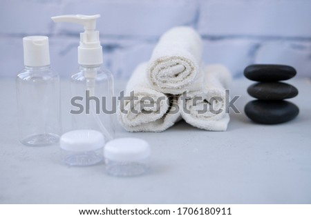Plastic containers. Spa composition, recreation and hospitality. Beauty and skin care concept.  Plastic bottles, lens containers and white towels on a light background #1706180911
