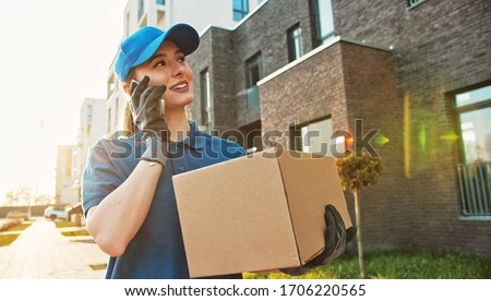 Caucasian young pretty woman, delivery worker in blue hat cap walking the street, carrying cardbox parcel and talking on mobile phone. Female beautiful courier with carton box speaking on cellphone. Royalty-Free Stock Photo #1706220565