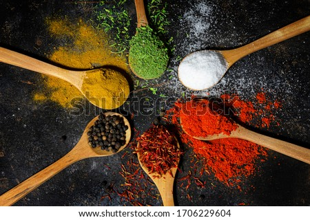 Variety of spices and herbs on black background Royalty-Free Stock Photo #1706229604