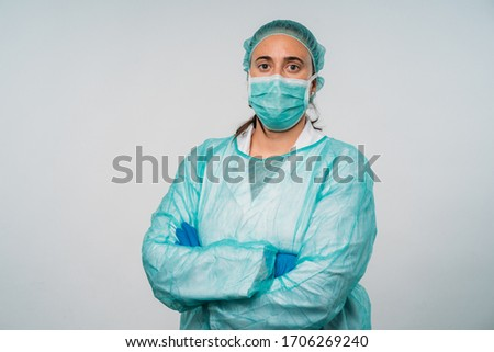 COVID-19 Coronavirus pandemic happy doctor positive with hope wearing surgical mask and protective scrubs at hospital. Inspiring confidence in the future to solve the crisis. #1706269240